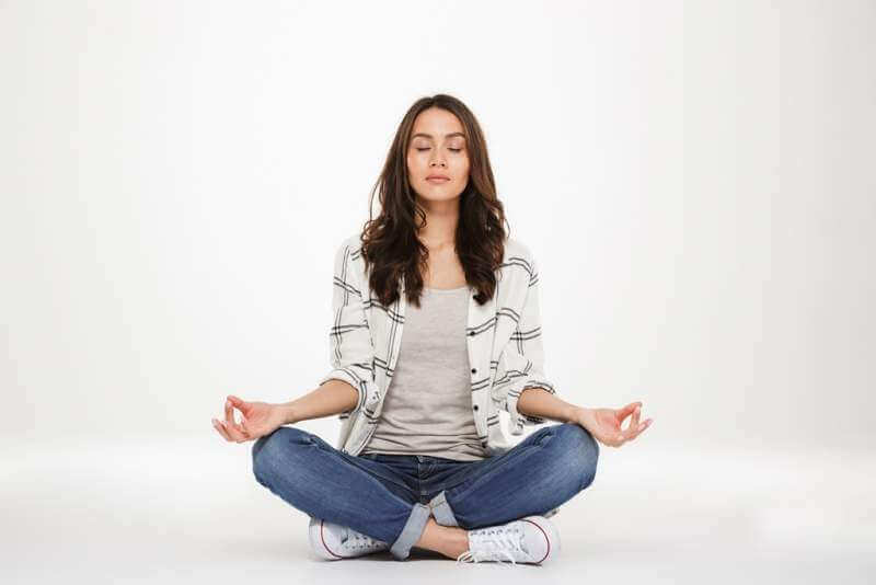 concentrated woman in casual clothes meditating with closed eyes while sitting in lotus pose on the floor