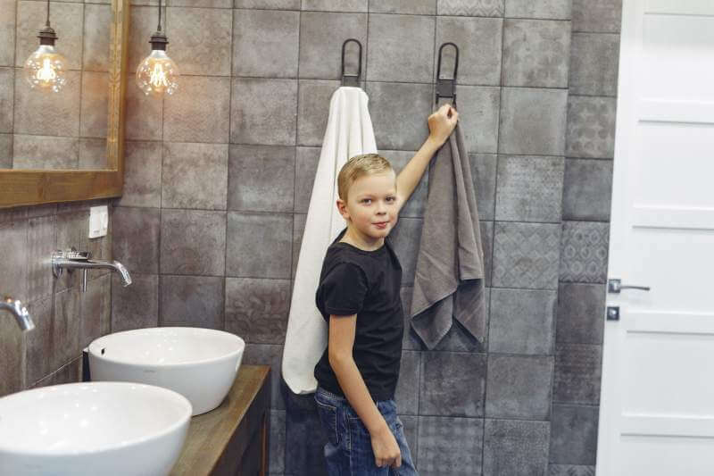 small-boy-hanging-up-towel-in-bathroom